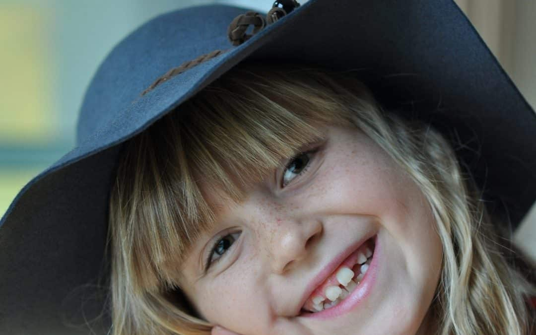 Picture of smiling child wearing a hat. Healthy Teeth.